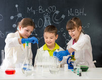 Three little students on chemistry lesson in lab. Doing an experiment Royalty Free Stock Images