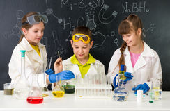 Three little students on chemistry lesson in lab Royalty Free Stock Photos