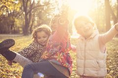 Three happy girls in park. Three Little three girls playing in park together. Looking at camera Stock Photos
