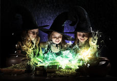 Three little witches. Three little Halloween witches reading conjure from magic book above pot Stock Photo
