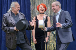 Three lively performers on stage. Celebrating in front of a microphone with a vivacious redhead women and two gentlemen with top hats laughing and joking Royalty Free Stock Images