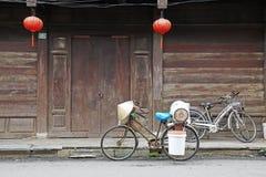Three local bicycles in front of wooden door stock image