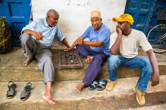 Three Local men are playing traditional board game Mancala. Stone Town, old colonial center of Zanzibar City, Unguja, Tanzania. stock image