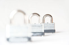 Three locked padlocks isolated Stock Photos