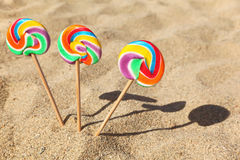 Three lollipops sticked in sand on beach Royalty Free Stock Images