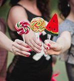 Three lollipops in women's hands. Three colorful candy in women's hands Royalty Free Stock Photography