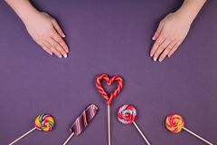 Three lollypops and manicure. royalty free stock photo