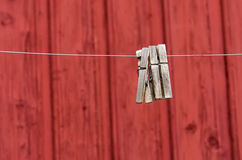 Three lone clothespins on red wall background Stock Photo