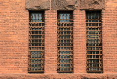 Three long barred windows in old brick wall Stock Photography