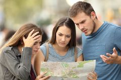 Three lost tourists trying to find a location in a map. Three worried lost tourists trying to find a location in a paper map on the street stock image