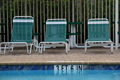 Three lounge chairs at pool Royalty Free Stock Photography
