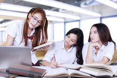 Three lovely female learners studying in class Royalty Free Stock Images