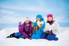 Three lovely girls with heart made of snow Stock Image