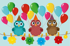 Three lovely owls sit on a rope and hold balloons. Royalty Free Stock Photography