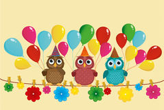 Three lovely owls sit on a rope and hold balloons. Royalty Free Stock Photos