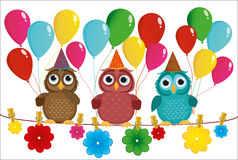 Three lovely owls sit on a rope and hold balloons. Stock Photo