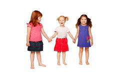 Three lovely smiling little girls holding hands. Redhead, blonde and brunette. Isolated on white background stock images