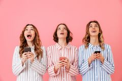 Three lovely young girls 20s wearing colorful striped pyjamas lo. Oking upward and using cell phones during happy sleepover isolated over pink background Stock Images