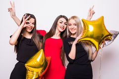 Three lovely young women have fun and holding star shaped balloons over white Stock Photo