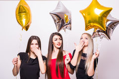 Three lovely young women have fun and holding star shaped balloons over white Royalty Free Stock Image