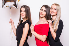 Three lovely young women in night dresses on side and holding star shaped balloons over white Royalty Free Stock Image