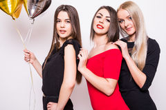 Three lovely young women in night dresses on side and holding star shaped balloons over white Royalty Free Stock Photography