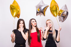 Three lovely young women standing and holding star shaped balloons over white Royalty Free Stock Photos