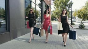 Three lovely young women walking down the street and enjoying their shopping day stock footage