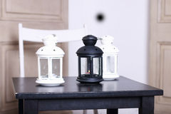 Three luminaire two white and one black on black wooden table. S Royalty Free Stock Image