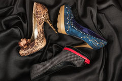 Three luxurious women`s shoes with high heels lying on a black silk. Royalty Free Stock Images