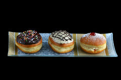 Three luxury sufganiyot with different icing on a decorative pla Stock Photo