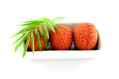 Three Lychee in a Dish. Three lychee and a green leaf in a dish with clipping on a white background Royalty Free Stock Image