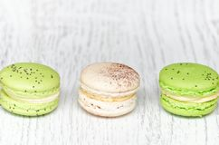 Three macarons on a light wooden table. Close up.  Royalty Free Stock Image