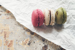 Three macaroon cakes on crumpled paper and rustic table Stock Photos