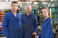 Three machinists in workspace by machine Royalty Free Stock Images