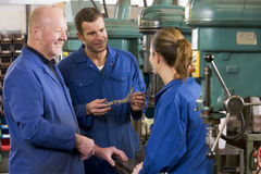 Three machinists in workspace by machine talking Stock Photo