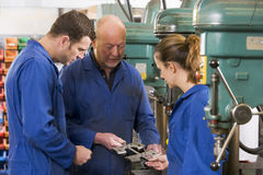 Three machinists in workspace by machine talking Royalty Free Stock Photos