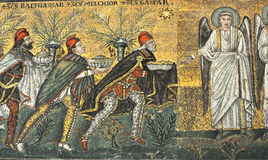 Three Magi. The three magi present their gifts to an angel in the nativity scene. Ancient UNESCO listed mosaic from Ravenna, Italy Royalty Free Stock Image