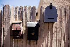 Three Mailboxes. Set in an old wood fence Royalty Free Stock Photography