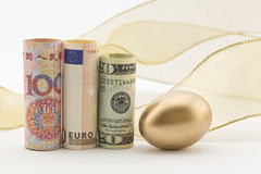 Three major currencies with gold egg Royalty Free Stock Photography
