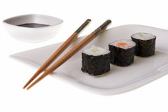 Three makizushi sushirolls. And chopsticks on a plate. Soy sauce. Isolated on white Stock Photos