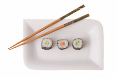 Three makizushi sushirolls and chopsticks. On a plate. Isolated on white Royalty Free Stock Photos