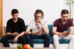 Three male friends cheking up their phones Stock Photography