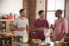 Three male friends drinking homemade smoothies in kitchen Royalty Free Stock Images