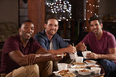 Three male friends eating a Chinese take-away look to camera Stock Photography