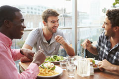 Three Male Friends Enjoying Lunch At Rooftop Restaurant Royalty Free Stock Photos