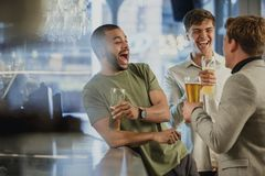 Enjoying Drinks After work. Three male friends are enjoying themselves at the bar after work, drinking pints of lager Royalty Free Stock Photo