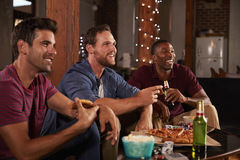 Three male friends hang out watching TV and eating pizza Stock Photography