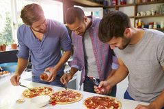 Three Male Friends Making Pizza In Kitchen Together Stock Photos