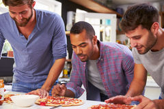 Three Male Friends Making Pizza In Kitchen Together Royalty Free Stock Photography
